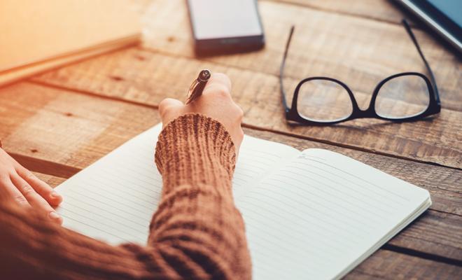 Imagen de una persona escribiendo sobre una mesa de madera